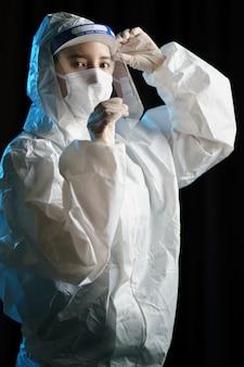 Frau, die handschuhe, biohazard-schutzanzug, gesichtsschutz und maske trägt. für corona-virus oder covid-19-schutz.