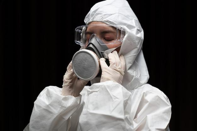 Frau, die handschuhe mit chemischem schutzanzug und maske der biologischen gefahr trägt.