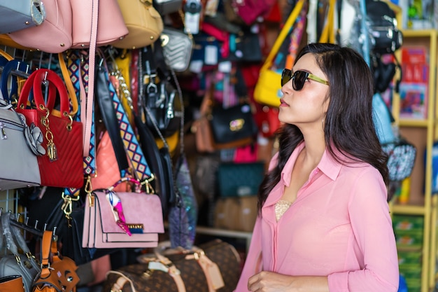 Frau, die handtasche im speicher wählt und kauft