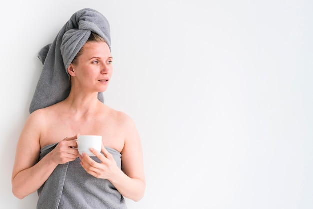 Frau, die handtücher trägt und eine tasse kopienraum hält