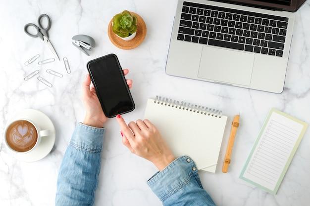Frau, die handy-anwendung mit computer-laptop verwendet. flache lage und moderner stil.