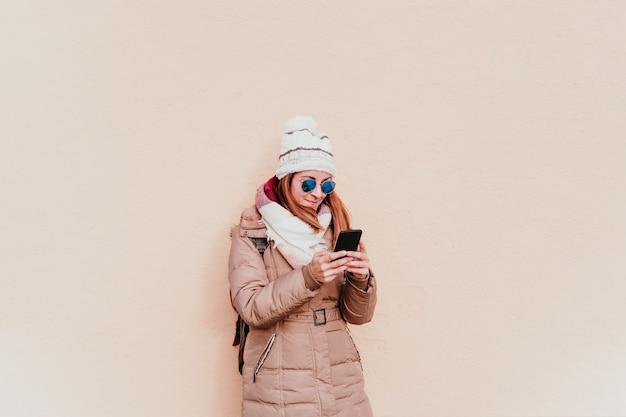 Frau, die handy auf gelber wand benutzt. technologie- und winterkonzept