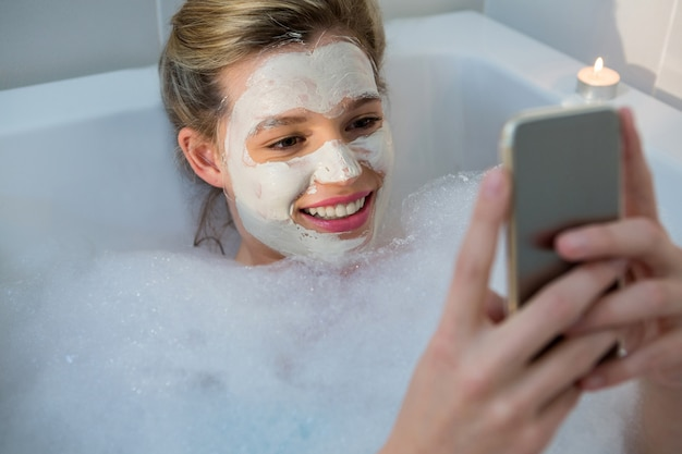 Frau, die handy beim baden in der badewanne benutzt