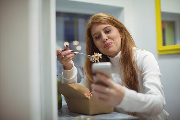 Frau, die handy beim essen salat verwendet