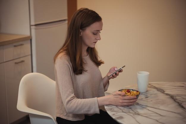 Frau, die handy beim frühstück in der küche verwendet