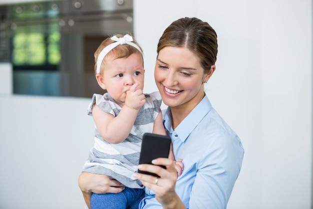 Frau, die handy beim tragen des babys verwendet