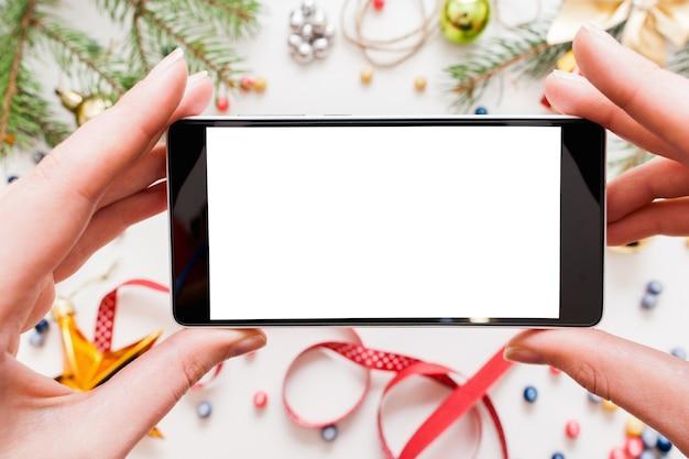 Frau, die handy hält und fotografie der weihnachtsdekoration macht
