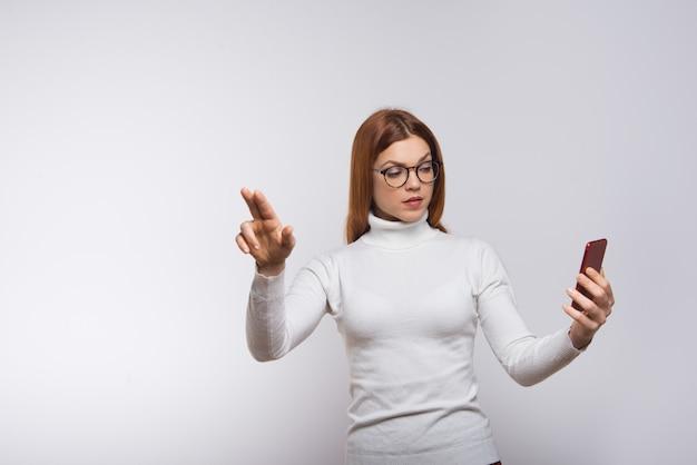 Frau, die handy hält und virtuellen knopf drückt