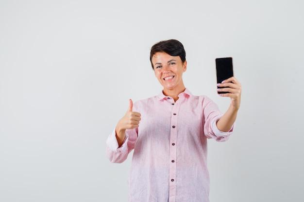 Frau, die handy hält, zeigt daumen oben in rosa hemd und sieht fröhlich aus. vorderansicht.