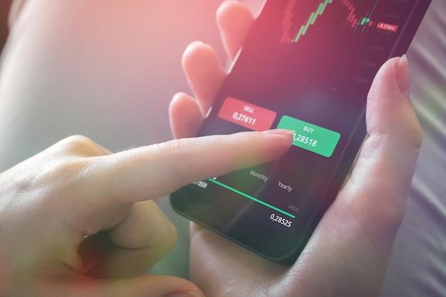 Frau, die handy-investitionsanwendung für den handel verwendet. kaufen und verkaufen sie mit der mobilen app. bildschirm mit finanzleuchtern, nahaufnahmefoto