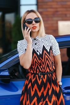 Frau, die handy, kommunikation oder online-anwendung verwendet, in der nähe von auto auf stadtstraße oder parkplatz, im freien stehend. carsharing, mietservice