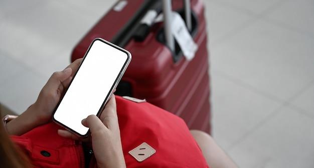Frau, die handy mit einem roten gepäck für das reisen in terminalflughafen verwendet