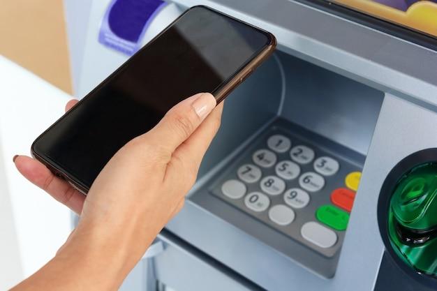 Frau, die handy mit schwarzem bildschirm und einer kreditkarte an einem atm hält