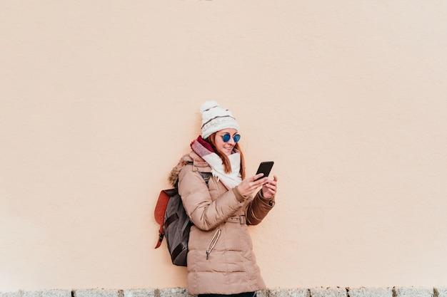 Frau, die handy über gelber wand benutzt. technologie- und winterkonzept