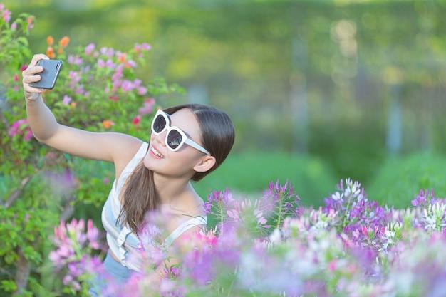 Frau, die handy verwendet, um foto im blumengarten zu machen.