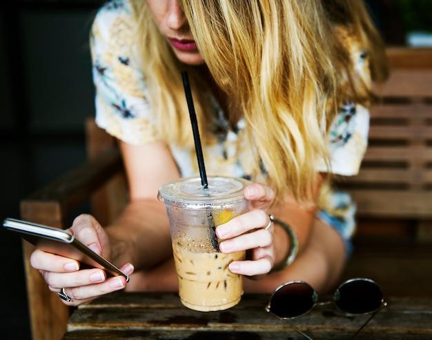 Frau, die handy verwendet und sich am café entspannt