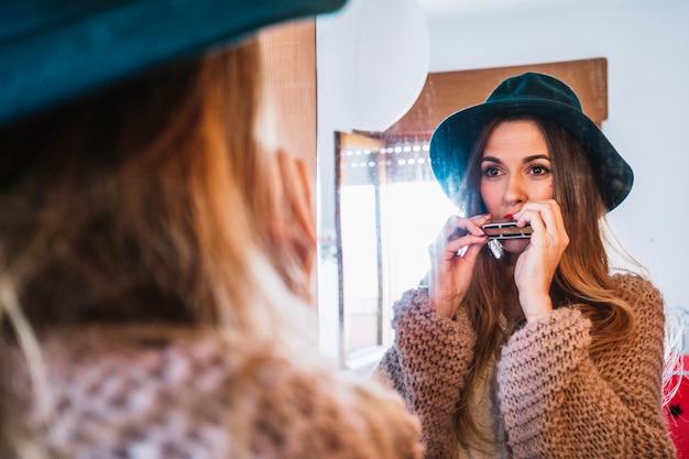 Frau, die harmonika nahe spiegel spielt