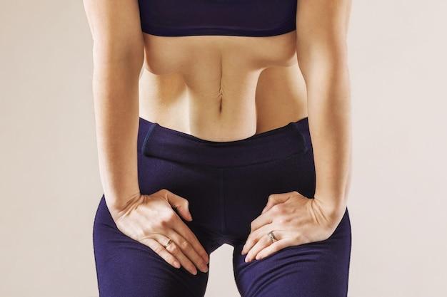 Frau, die hatha yoga praktiziert, führt die übung nauli wellige bewegung der bauchmuskeln durch