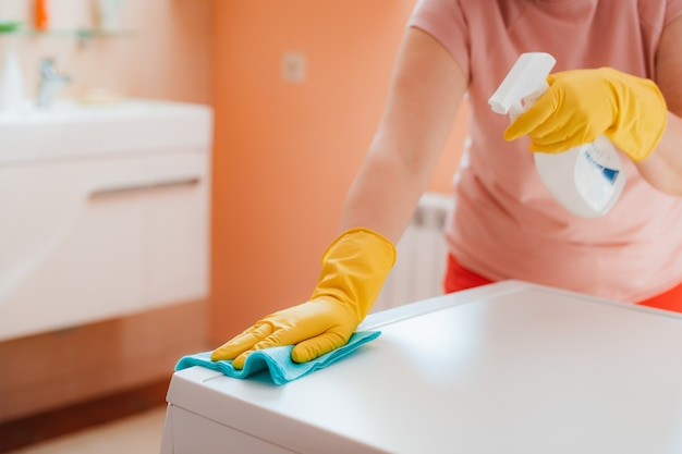 Frau, die hausarbeit im badezimmer zu hause tut, oberflächen reinigend