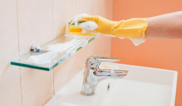 Frau, die hausarbeit im badezimmer zu hause tut