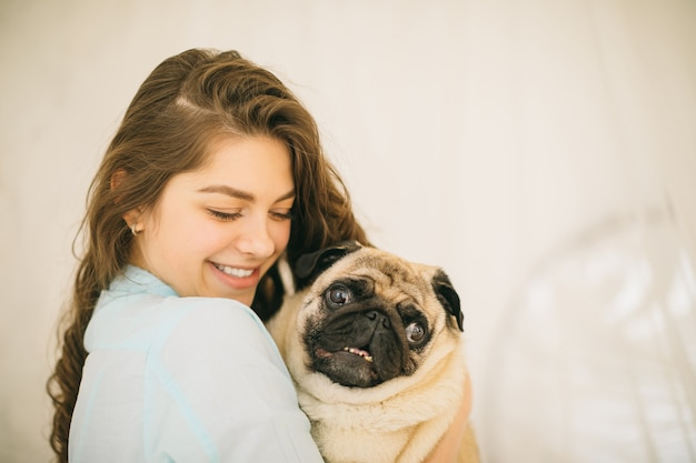 Frau, die haustier pug umarmt. schönes familienporträt