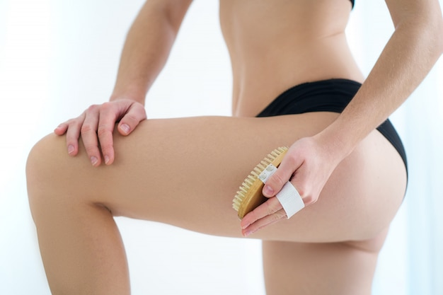 Frau, die haut gesäß und hintern mit einer trockenen holzbürste bürstet, um cellulite und körperprobleme nach dem duschen zu hause zu verhindern und zu behandeln. hautgesundheit