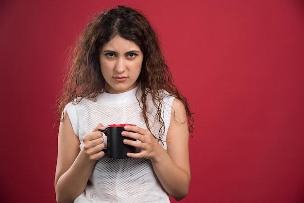 Frau, die heiße dunkle tasse auf rot hält