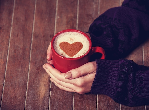 Frau, die heiße tasse kaffee mit herzform hält