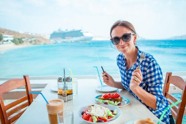 Frau, die heißen kaffee auf luxushotelterrasse mit seeansicht am erholungsortrestaurant trinkt
