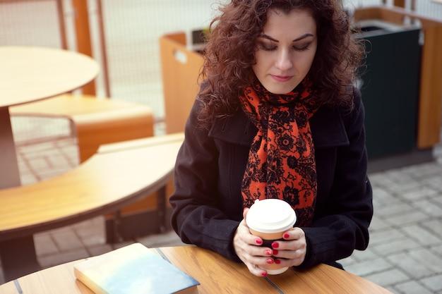 Frau, die heißen kaffee beim lesen eines buches trinkt