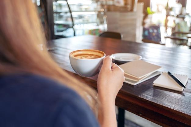 Frau, die heißen kaffee mit notizbüchern auf tisch im café hält und trinkt