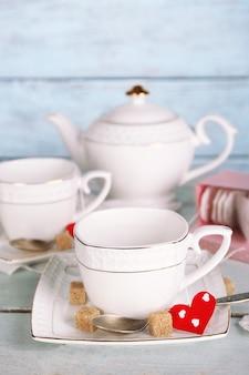 Frau, die heißen tee von der teekanne in den hölzernen hintergrund der tasse gießt