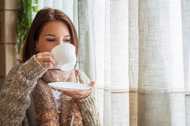 Frau, die heißen tee während des winters trinkt