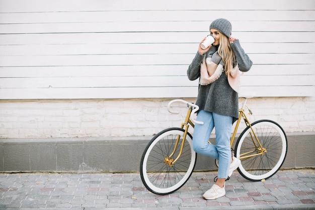 Frau, die heißgetränk nahe fahrrad trinkt