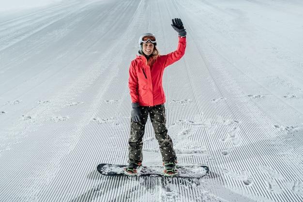Frau, die helm mit snowboard auf der skipiste trägt. abendreiten