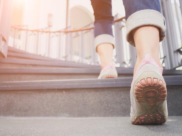 Frau, die herauf die treppe mit sonnensporthintergrund geht.