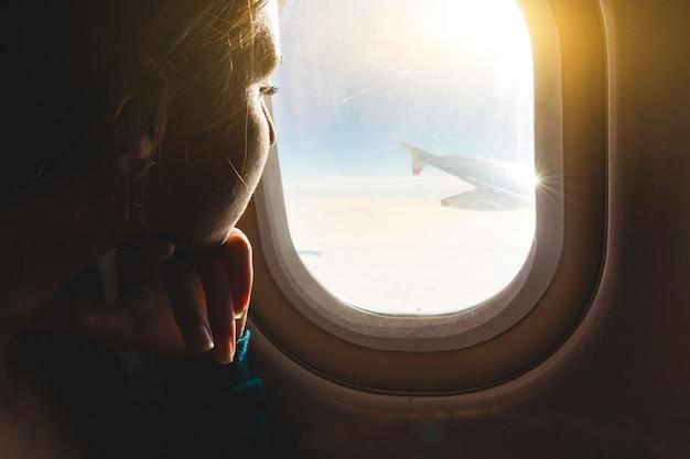 Frau, die heraus durch flugzeugfenster schaut