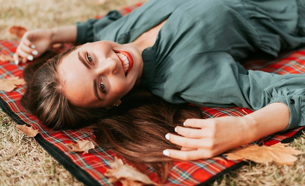 Frau, die herbst auf einer picknickdecke genießt