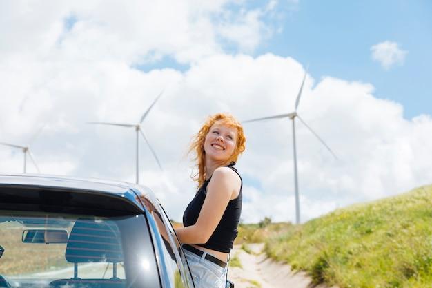 Frau, die herum aus autofenster am sonnigen tag heraus schaut