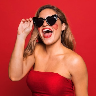 Frau, die herzförmige sonnenbrille trägt