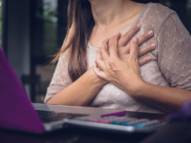 Frau, die herzinfarkt hat. rührende brust der frau und brustschmerzen habend