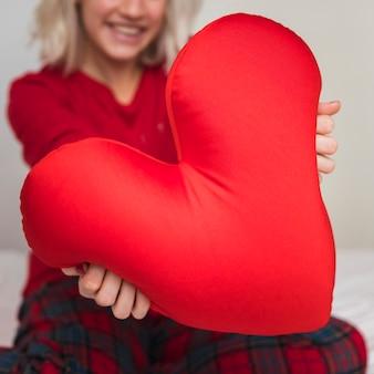Frau, die herzkissen am valentinstag umarmt