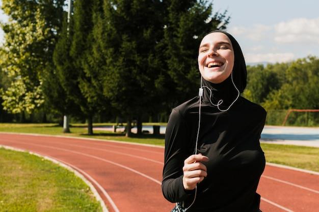 Frau, die hijab an der laufbahn trägt