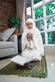 Frau, die hijab trägt, der koran liest