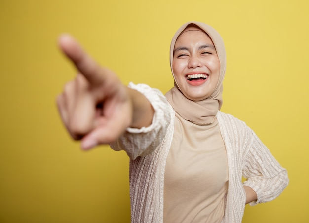 Frau, die hijab trägt, zeigt auf jemanden, der auf einer gelben wand isoliert wird