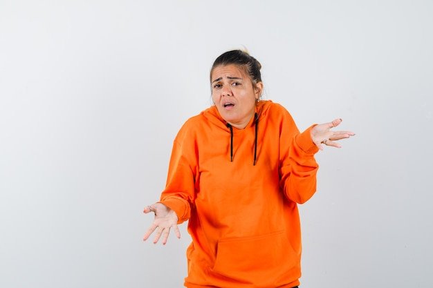 Frau, die hilflose geste in orangefarbenem hoodie zeigt und verwirrt aussieht