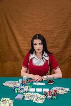 Frau, die hinter pokertisch im kasino sitzt
