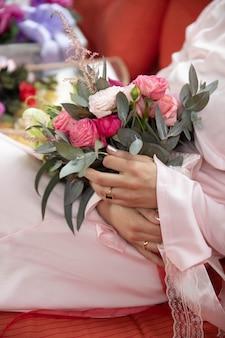 Frau, die hochzeitsblumen im raum im langen rosa kleid und in den roten fersen sitzt und hält.