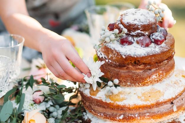 Frau, die hochzeitsgebäckkuchen mit frischen blumen verziert.