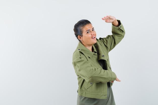 Frau, die höhenzeichen in jacke, t-shirt zeigt und selbstbewusst aussieht